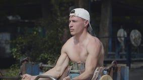 Athletischer Mann, der den Barbell im Park anhebt ?bung f?r Bizeps Schlie?en Sie herauf Portrait Entspannung durch pilates Kugel  stock video