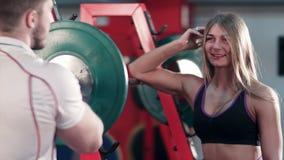 Athletischer Mann, der den Blondinen sein Bizeps in der Turnhalle zeigt stock video footage