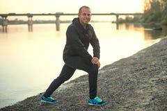 Athletischer Mann, der draußen Übung auf dem Strand bei Sonnenuntergang tut Lizenzfreie Stockfotos