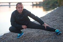 Athletischer Mann, der draußen Übung auf dem Strand bei Sonnenuntergang tut Stockfotografie