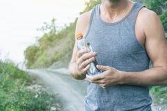 Athletischer Mann, der eine Flasche Wasser, stehend auf dem Ozean hält Sport und ein gesunder Lebensstil stockfotografie