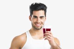 Athletischer Mann, der einen Saft trinkt Stockfotos