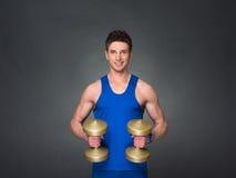 Athletischer Mann der hübschen Energie im Training, das oben pumpt, mischt mit Dummköpfen in einer Turnhalle mit Stockfotografie