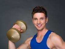 Athletischer Mann der hübschen Energie im Training, das oben pumpt, mischt mit Dummköpfen in einer Turnhalle mit Stockfotos