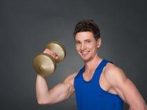Athletischer Mann der hübschen Energie im Training, das oben pumpt, mischt mit Dummköpfen in einer Turnhalle mit Lizenzfreie Stockfotos