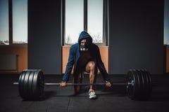 Athletischer Mann in der Jacke mit einer Haube, die bevor der schwere Barbell wartet und sich vorbereitet, der, Kamera betrachtet Stockbilder