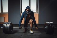 Athletischer Mann in der Jacke mit einer Haube, die bevor der schwere Barbell wartet und sich vorbereitet, der, Kamera betrachtet Lizenzfreies Stockfoto