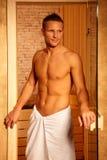 Athletischer Mann an der Saunatür Stockbild