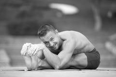 Athletischer Mann, der Yoga asanas im Park tut Lizenzfreie Stockfotos