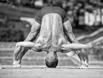 Athletischer Mann, der Yoga asanas im Park tut Stockbild