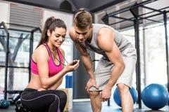 Athletischer Mann, der Zeit mit Trainerfrau überprüft Lizenzfreie Stockfotografie