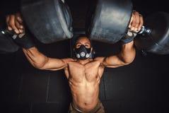 Athletischer Mann des Afroamerikaners in anhebenden Dummköpfen der Maske und Arbeiten an seiner Kastenansicht von oben schwarzer  Lizenzfreie Stockfotografie
