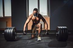 Athletischer Mann des Afroamerikaners, der bevor der schwere Barbell wartet und sich vorbereitet, der, Kamera betrachtet angehobe Stockfotografie