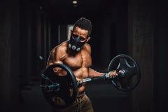 Athletischer Mann des Afroamerikaners in der Maske, die Kamera betrachtet und Barbell auf Bizeps anhebt Übung für Bizeps mit Barb Stockbilder