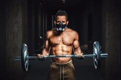Athletischer Mann des Afroamerikaners in der Maske, die Kamera betrachtet und Barbell auf Bizeps anhebt Übung für Bizeps mit Barb Stockbild