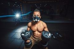 Athletischer Mann des Afroamerikaners in der Maske, die Kamera sitzt und wartet und betrachtet, bevor Dummköpfe vor dem Spiegel a Lizenzfreies Stockbild
