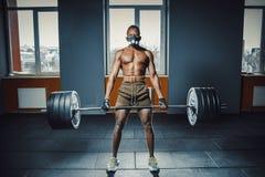 Athletischer Mann des Afroamerikaners in der Sportmaske, die deadlift mit schwerem Barbell tut schwarzer Mann anhebender Barbell  Stockfoto