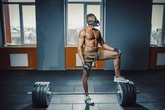 Athletischer Mann des Afroamerikaners in der Sportmaske setzte seinen Fuß auf den Barbell, der bevor er schweren Barbell wartet u Lizenzfreie Stockbilder