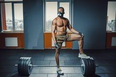 Athletischer Mann des Afroamerikaners in der Sportmaske setzte seinen Fuß auf den Barbell, der bevor er schweren Barbell wartet u Stockbilder