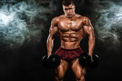Athletischer Mann des groben starken muskulösen Bodybuilders, der oben Muskeln mit Dummkopf auf schwarzem Hintergrund pumpt worko lizenzfreie stockfotografie