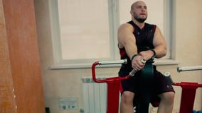 Athletischer Mann in einer Turnhalle, die an einem Simulator arbeitet stock video footage
