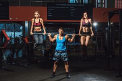Athletischer Mann hebt Barbell mit zwei Mädchen als Gewicht und den Mädchen, die vom Barbell hängen an Barbell mit zwei Mädchen a Stockfotos
