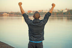 Athletischer Mann ist glücklich freuend und am Strand Lizenzfreie Stockfotos