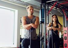 Athletischer Mann und Frau in einer Turnhalle Stockfoto