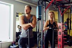 Athletischer Mann und Frau in einer Turnhalle Lizenzfreies Stockbild