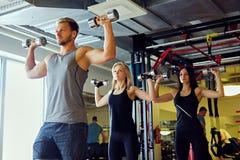 Athletischer Mann und zwei dünne weibliche Eignungsmodelle, die Schulterübungen mit Dummköpfen tun Stockbilder
