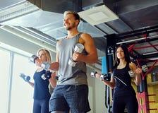 Athletischer Mann und zwei dünne weibliche Eignungsmodelle, die Schulterübungen mit Dummköpfen tun Stockfotos