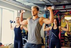 Athletischer Mann und zwei dünne weibliche Eignungsmodelle, die Schulterübungen mit Dummköpfen tun Lizenzfreie Stockbilder