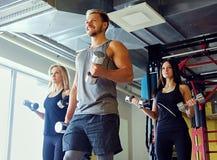 Athletischer Mann und zwei dünne weibliche Eignungsmodelle, die Schulterübungen mit Dummköpfen tun Stockbild