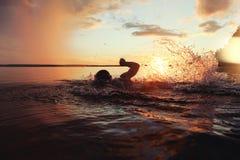 Athletischer Mann wird ausgebildet, um in einem See bei Sonnenuntergang zu schwimmen Es fliegt viel Wasserspritzen Stockfotografie