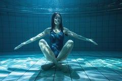 Athletischer Schwimmer, der unter Wasser an der Kamera lächelt Lizenzfreie Stockfotografie