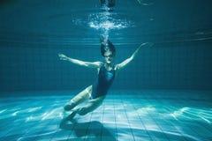 Athletischer Schwimmer, der unter Wasser an der Kamera lächelt Stockfotografie