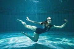 Athletischer Schwimmer, der unter Wasser an der Kamera lächelt Stockbild