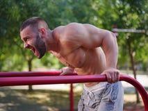 Athletischer, sexy Bodybuilder des gutaussehenden Mannes, der auf einem unscharfen Hintergrund ausarbeitet Gebäude mischt Konzept Stockbild