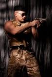 Athletischer Soldat, der mit Pistole zielt Stockfotos