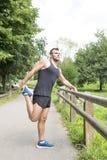Athletischer starker Mann, der Ausdehnungen bevor dem Trainieren, im Freien tut stockfoto
