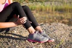 Athletischer verstauchter Fuß der jungen Frau Stockfotografie