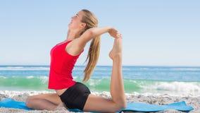 Athletisches blondes ausdehnendes Bein in der Yogahaltung Stockbild
