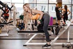 Athletisches blondes Mädchen mit dem langen Haar, das in einer Sportkleidung gekleidet wird, tut Übung auf der Bank mit Dummköpfe stockfoto