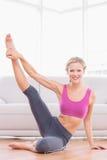Athletisches blondes Sitzen auf dem Boden, der das Bein oben lächelt an der Kamera ausdehnt Lizenzfreie Stockfotos