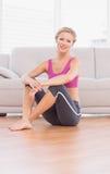 Athletisches blondes Sitzen auf dem Boden, der an der Kamera lächelt Lizenzfreie Stockfotografie