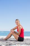 Athletisches blondes Sitzen auf dem Sand, der an der Kamera lächelt Lizenzfreies Stockfoto