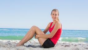 Athletisches blondes Sitzen und Lächeln an der Kamera Stockfotografie