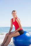 Athletisches junges blondes Sitzen auf dem Übungsball, der Kamera betrachtet Lizenzfreies Stockfoto