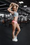 Athletisches junges sexy blondes Mädchen, das in der Turnhalle aufwirft und Stockfotos