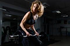 Athletisches junges sexy Mädchentraining mit Gewicht in der Turnhalle Lizenzfreies Stockfoto